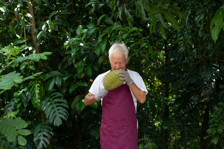 Man examining durian while standing against trees