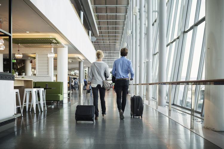 Rear view of people walking in airport