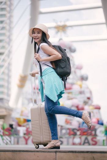 Tourist with luggage standing on steps in city during christmas
