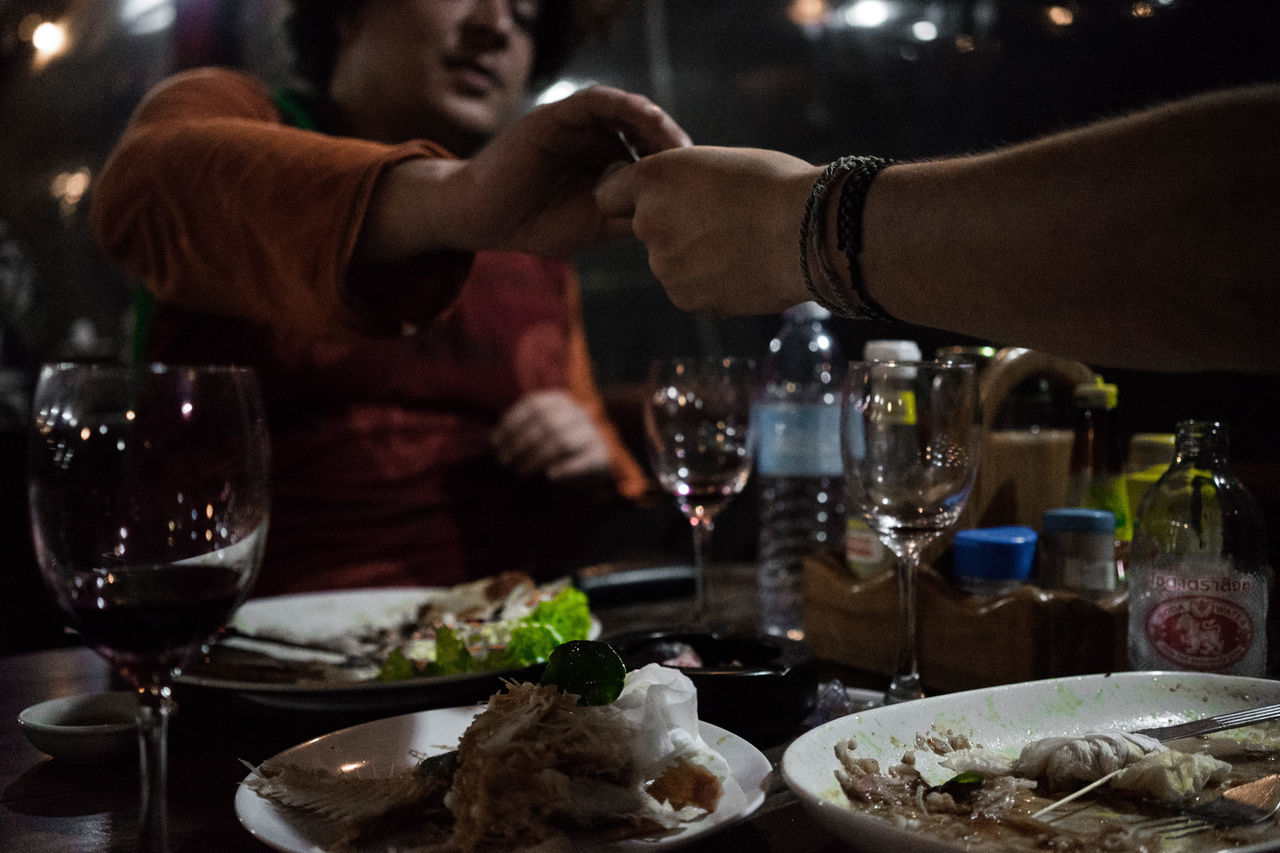 People holding hand over dining table
