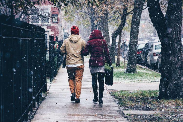 Rear view of people walking on street during snowfall