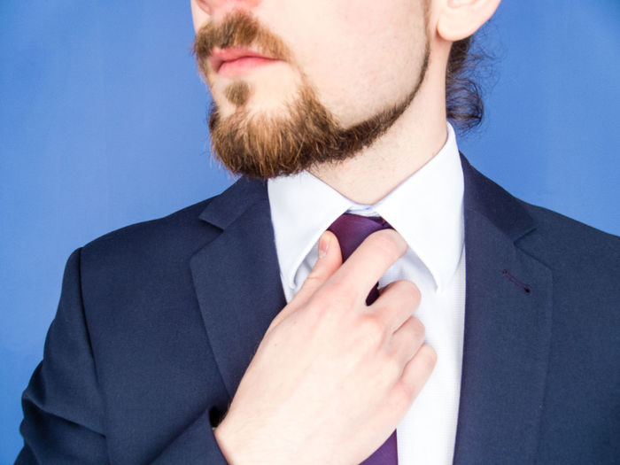 Midsection Of Businessman Adjusting Tie Against Blue Background