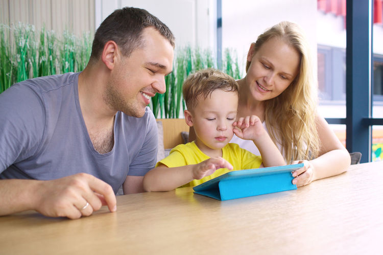 Boy Cafe Cafeteria Caucasian Child Childhood Computer Father Happiness Horizontal Ipad Kid Mother Pad Parent Play Restaurant Son TAB Three Touch Pad Touchpad Use