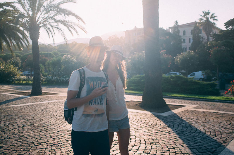 Young Couple Wearing Hats Standing On Paved Boulevard