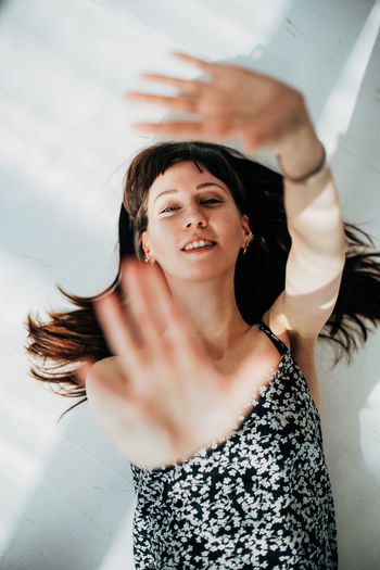 Portrait of smiling young woman gesturing against wall
