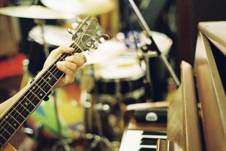 Cropped man playing guitar in recording studio