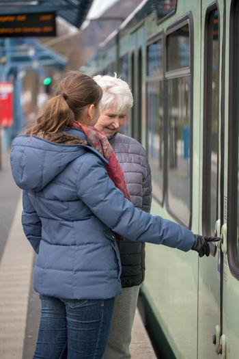 Granddaughter Teaching Grandmother Opening Door Of Train