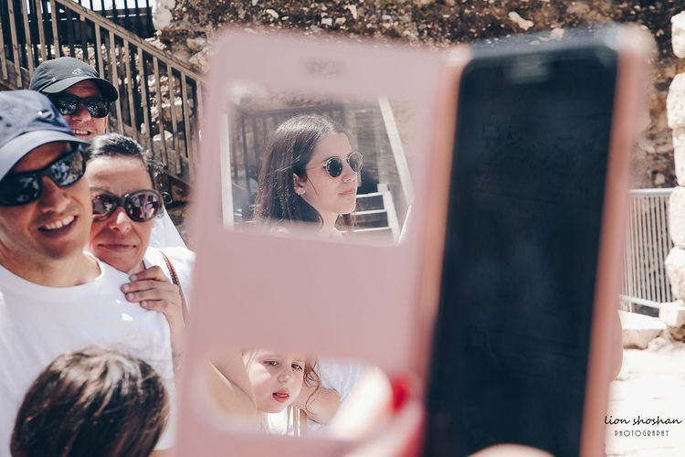 Reflection of young woman using mobile phone in mirror