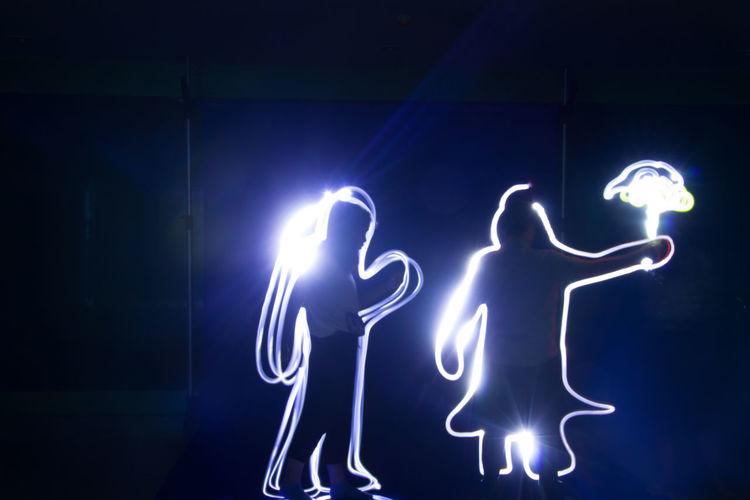 Illuminated light painting on wall at night
