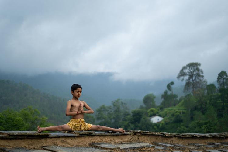 Full length of man sitting against mountains against sky