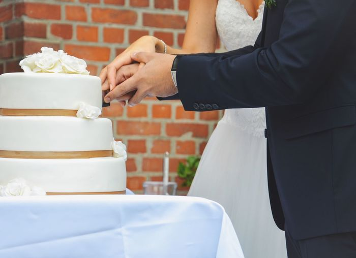 Midsection of newlywed couple cutting wedding cake in ceremony
