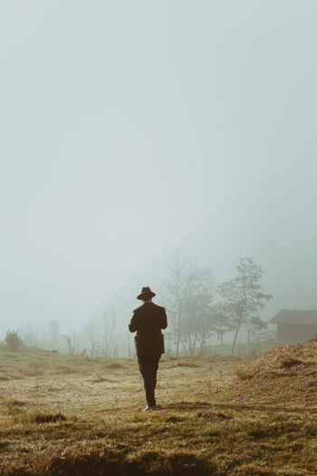 Man walking on land against sky