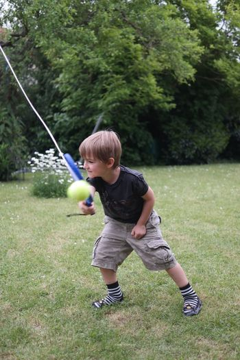 Side view of a boy playing on grassland