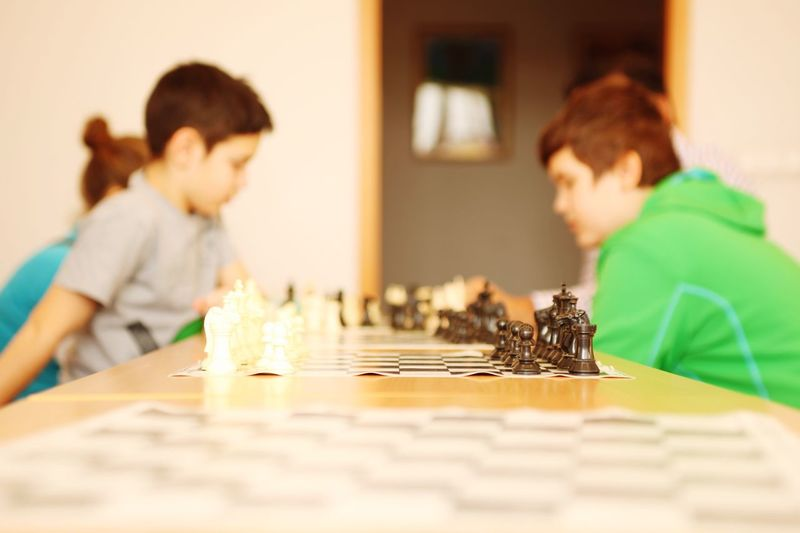 Boys playing chess on table at home