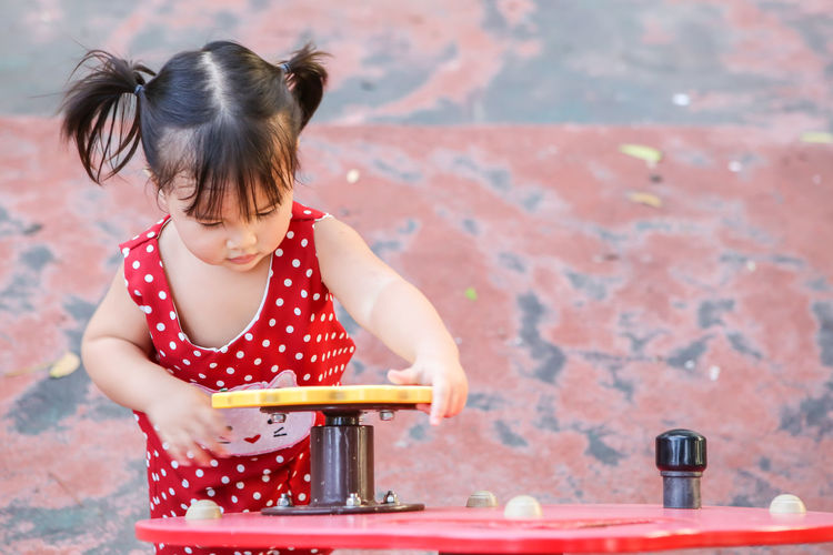 Cute girl playing yellow toy garlands on the playground