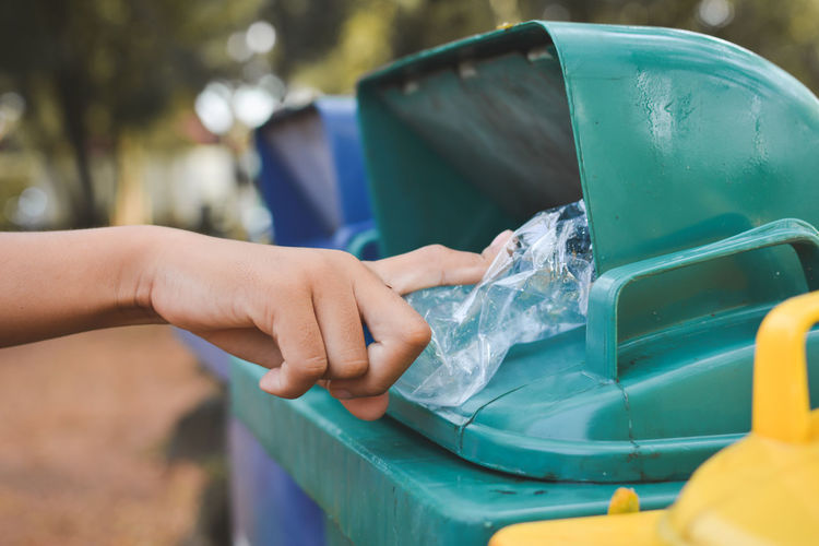Cropped hand putting plastic in garbage can
