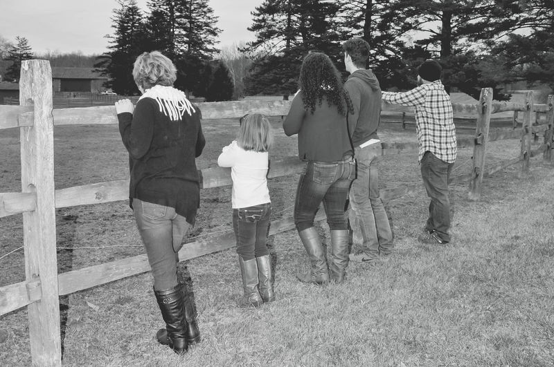 Family Standing Together by a Wood Fence in Black & White Children Family Man Relationship Woman Daughter Friendship Full Length Leisure Activity Lifestyles Nature Outdoors Parents People Real People Son Standing Togetherness