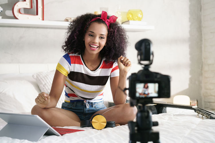 Portrait of smiling young woman using phone while sitting on bed