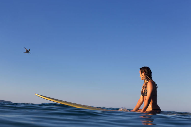 Woman Surfing In Sea Against Blue Sky