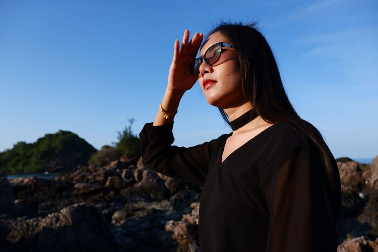 Woman shielding eyes while standing by rock against sky