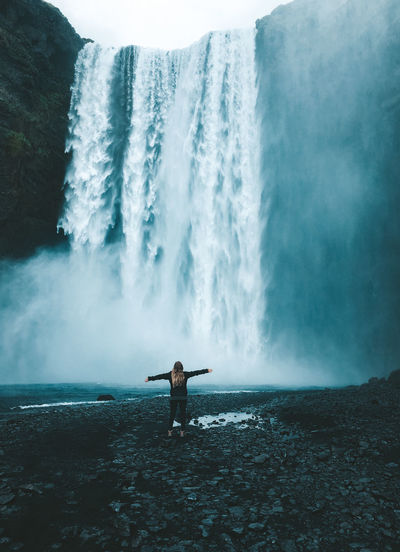 Rear View Of Woman With Arms Outstretched Standing By Waterfall