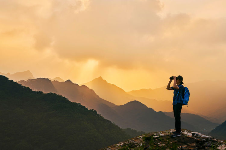 Man looking through binoculars while standing on mountain against sky during sunset
