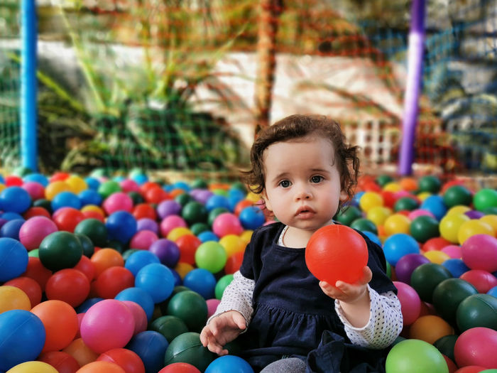Little baby playing alone in the ball pit.