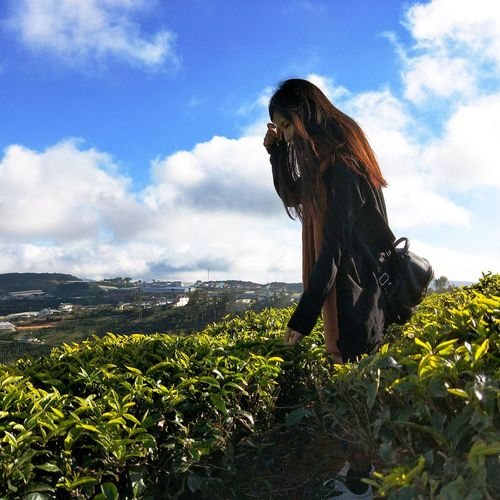 Woman with plants on landscape against sky