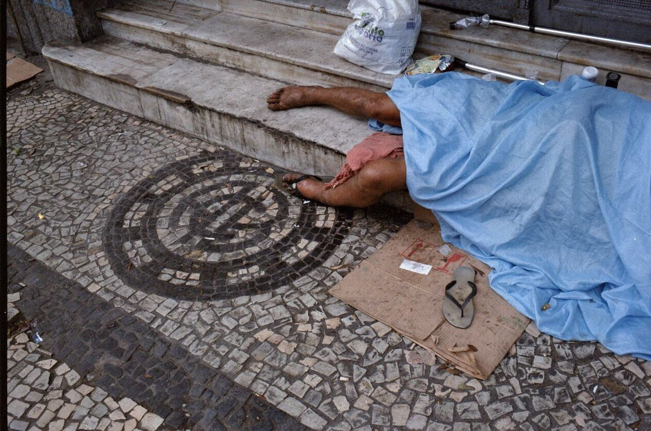 LOW SECTION OF MAN WITH UMBRELLA ON COBBLESTONE