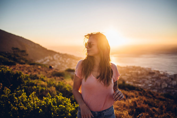 Beautiful woman standing on land against sky during sunset