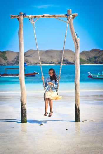 Portrait of girl on swing at beach against sky