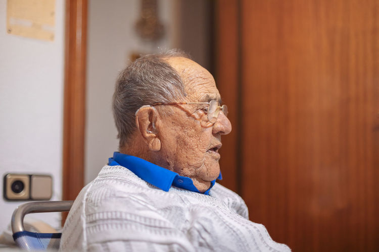 Close-up of senior man looking away while sitting at home