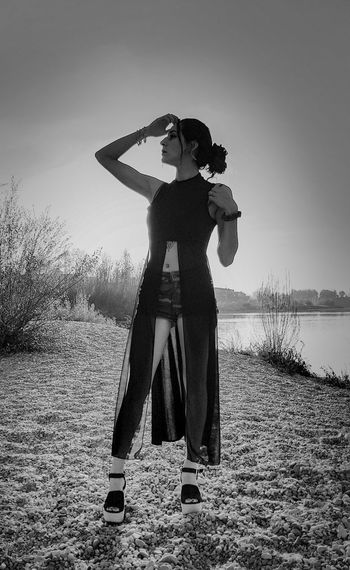 Woman standing at lakeshore against clear sky