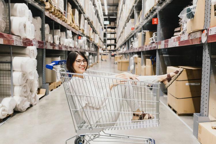Asian beautiful woman wearing glasses sitting in shopping cart at warehouse furniture shopping store