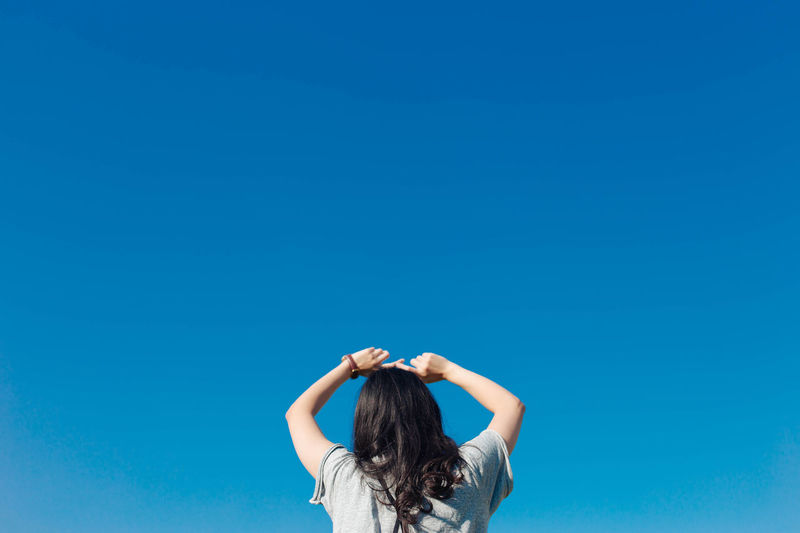 woman back arm raised in the air Arms Raised Blue Childhood Clear Sky Day Headshot Leisure Activity Lifestyles Low Angle View One Person Outdoors People Real People Rear View Sky Women Young Adult Young Women