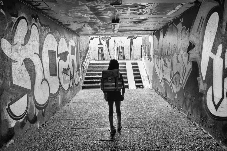 Rear view of student walking up an underground subway