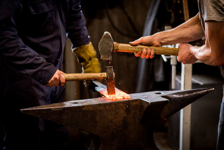 Two blacksmiths working on a red hot metal bar. Artisan Blacksmith  Blacksmith Shop Craft Forge  Hammer Industrial Making Men Metal Metalwork Skill  Strong Tradition Working Fresh On Market 2016