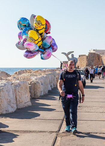 Aco, Israel, October 22, 2016: Street vendor sells balloons and beckoning shoppers on the waterfront in Aco, Israel Aco Adult Adults Only Air Ballons Beckoning Buisness City Cloud - Sky Day Individuality Israel Market One Person Outdoors People Sale Sea Sells Shoppers Street Toy Travel Vendor Waterfront