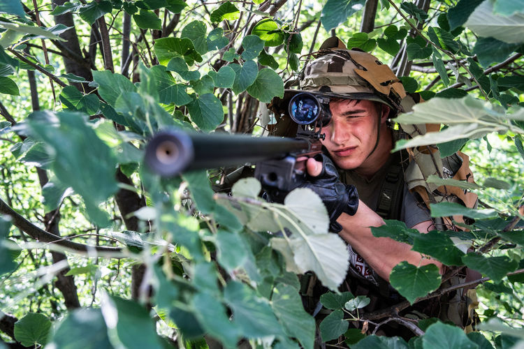Soldier holding gun by trees in forest