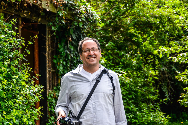 Portrait of smiling man holding camera while standing against trees