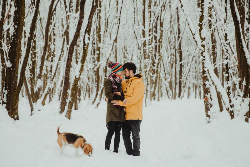 Couple in love with a beagle dog standing in forest during winter