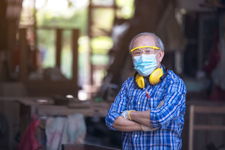 A mature carpenter standing confidently in his workshop