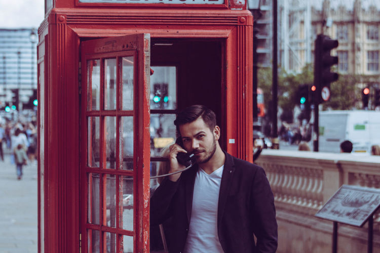 Portrait of businessman talking at telephone booth in city