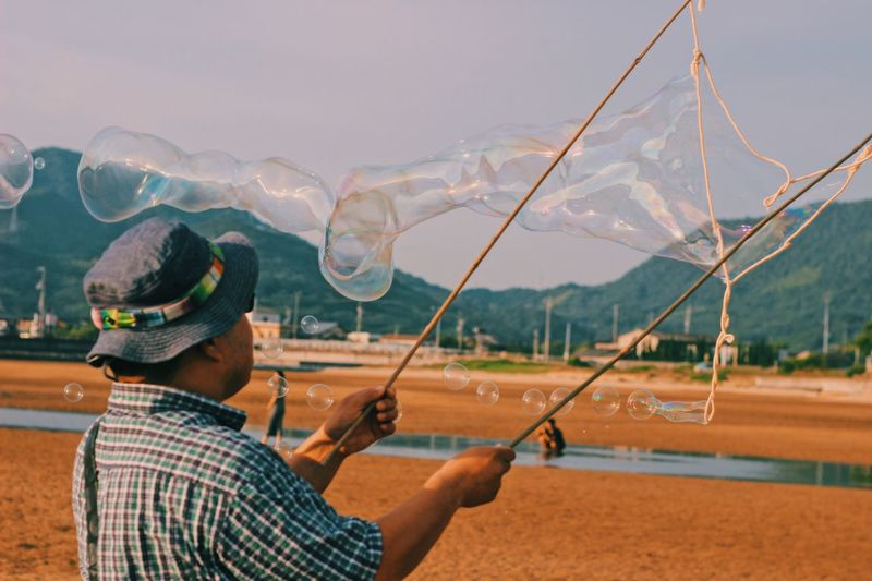 Mature Man Blowing Bubbles With Sticks And Ropes At Beach