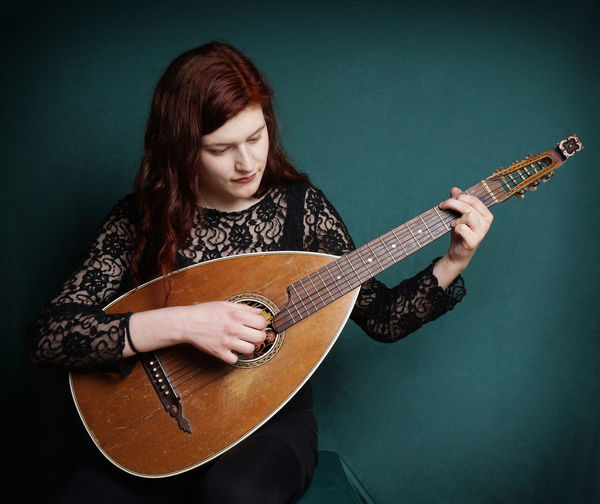 Young woman playing lute against green wall