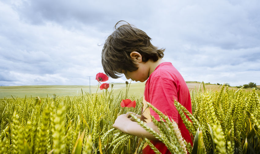 Side View Of Boy Standing Amidst Plants On Field Against Sky