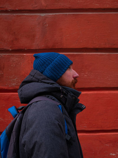 Bearded guy in blue hat coat on red wall background. urban style street photo active lifestyle hiker