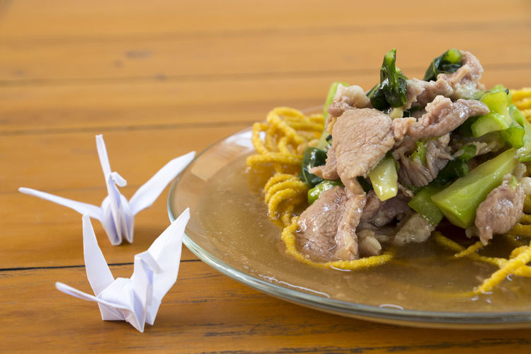 Close-up of meat salad on fried noodles in plate by origami at table