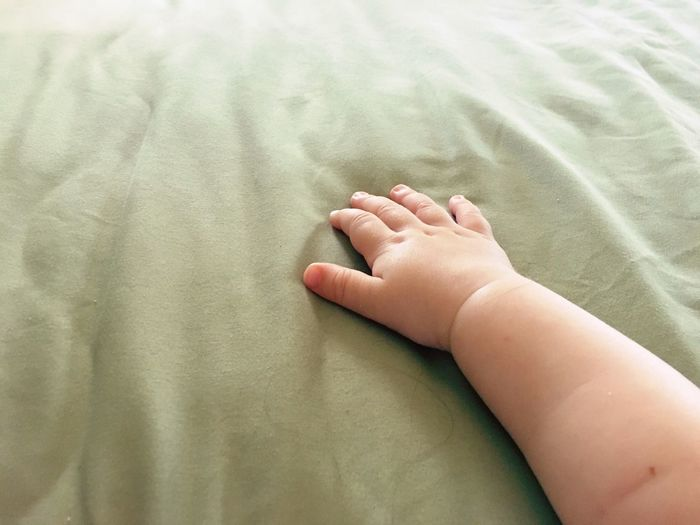 Cropped hand of baby on bed