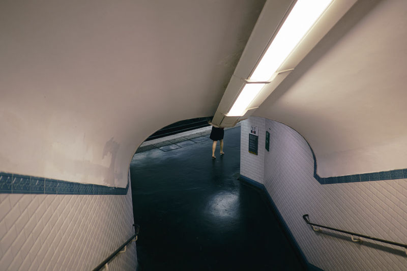 Low section of woman walking in illuminated subway station